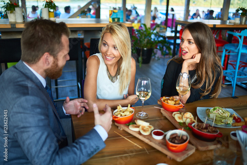 business people meeting in modern restaurant, colleagues having dinner and take drink after work - 123622443