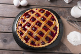 Homemade traditional sweet cherry  tart pie with  wooden table background.