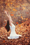 Autumn leaves falling on happy young woman in forest - 123659079