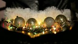 Christmas holiday toys with shiny garland on fir tree and black background.