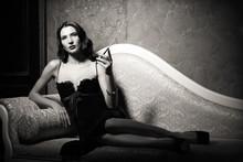 Film noir stylu: elegancki młoda kobieta, leżąc na kanapie i palenia papierosów. Czarny i biały