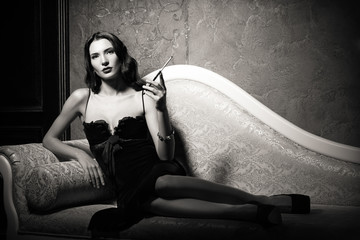 Film noir style: elegant young woman lying on sofa and smoking cigarette. Black and white