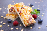 healthy snack, muesli bars with raisins and dried berries on a black background - 123671416