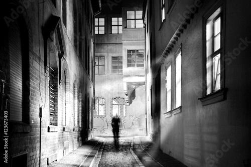 Foto op Aluminium Smal steegje Ein Mensch wandert durch eine gespenstische enge Gasse in der dunklen Nacht