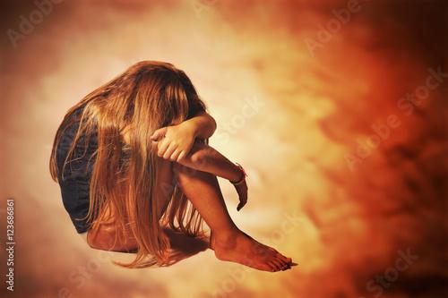 Poster Bambina triste rannicchiata su se stessa