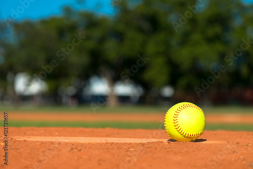 Yellow softball on pitchers mound Poster