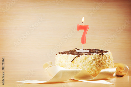 Poster Birthday cake with burning candle as a number seven