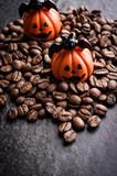 Halloween pumpkin decoration with coffee beans on dark background