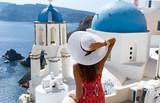 Frau in rotem Kleid schaut auf eine Kirche mit blauer Kuppel in Oia, Santorini - 123753667