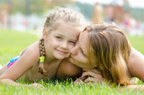 Mother kissing her daughter lying on a green grass lawn