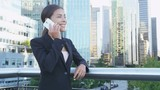 Smart phone woman calling on mobile phone in city business district. Confident young business woman talking on smartphone smiling happy wearing suit jacket outdoors. Urban female professional in 20s.