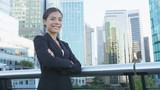 Business woman portrait of young female urban professional businesswoman in suit standing outside office building with arms crossed. Confident successful multicultural Chinese Asian / Caucasian woman.