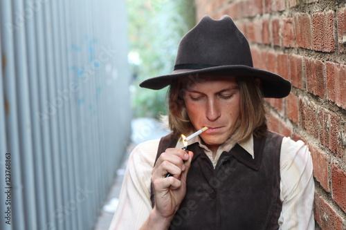 Poster Retro cowboy smoking cigarette. Young man lighting a cigarette