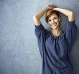 Happy young woman in blue jeans posing at wall