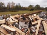 Топор воткнутый в чурбак около расколотых дров.