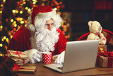 Fototapety Christmas. Santa Claus with laptop reading letter
