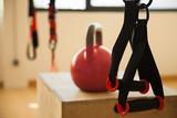 kettlebell y trx / Trx junto a kettlebell roja en centro deportivo