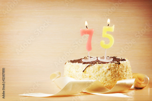 Birthday cake with burning candle as a number seventy five Poster