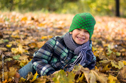 Poster Handsome and happy little boy playing with the leaves, they bear in park