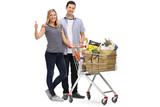 Couple posing with shopping cart giving thumb up