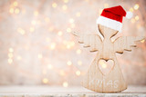 Christmas decor with angel santa hat. Vintages background.