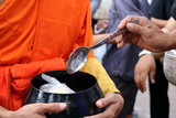 Hands of people while put food to a Buddhist monk