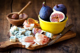 Italian appetizer or meat and cheese platter with fresh figs, cured ham prosciutto and spicy gorgonzola cheese against dark wooden background