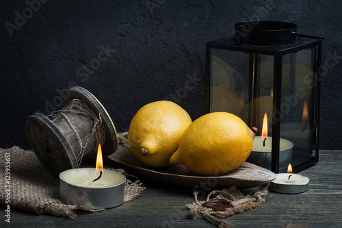 Still life with three lemons and coffee mill. Dark style