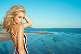 Portrait of chic blond woman in striped dress with naked back standing at the seaside and looking straight with predatory green eyes. Femme fatale. Hair care concept. Copy-space. Outdoor shot