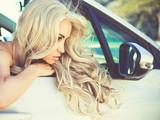 Atmospheric portrait of beautiful blonde in car