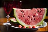 Куски арбуза на белой тарелке, на заднем плане - бокалы для вина из белого и красного стекла и белый заварной чайник