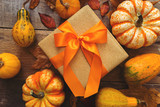 autumn gift in gold paper with orange ribbon