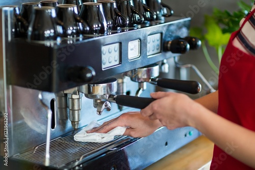 Poster Waitress wiping espresso machine with napkin in café