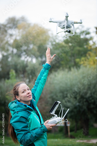 Poster Young woman holding radio controller and rising hand towards a drone in a nature