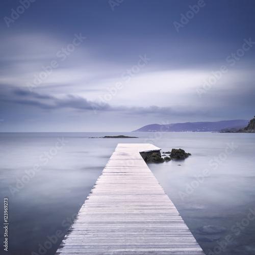 Obraz na Plexi Wooden pier, rocks and sea on misty sunset.