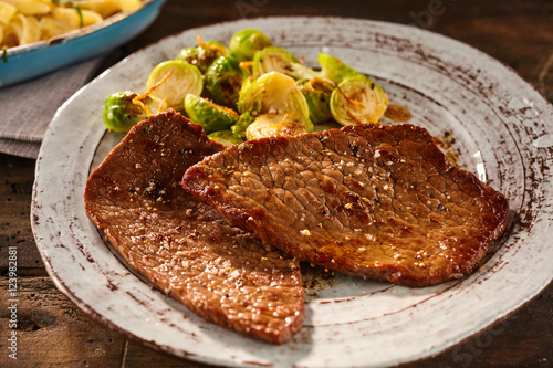 Serving of marinated and cooked minute steak with veggies