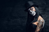 A girl in stylish top hat with skull make up. - 123984419