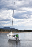 White yacht moored by a lakes shore.  Mountain range in the distance.