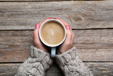 Woman hands holding cup of coffee on wooden table