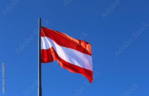 great Austrian flag waving in the blue cloudless sky