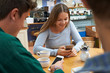 Group Of Teenage Friends Meeting In Cafe And Using Mobile Phones