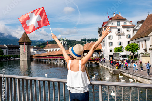 Young female traveler with raised hands holding a swiss flag standing in front o Poster