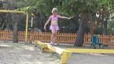 Little girl walking on wooden beam on the playground.