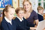 Teacher Helping Elementary School Pupils In Computer Class