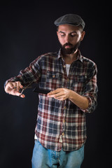 Barber holding scissors and comb. On a black background.
