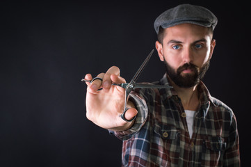 Barber holding scissors in hand. On a black background.