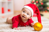 Funny baby wearing Santa hat and suit. Kid boy lying on tummy in front of Christmas tree