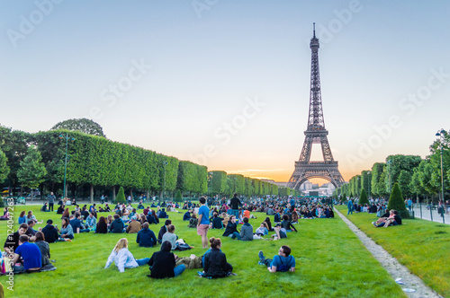 Poster Eiffel Tower and people sitting on the grass watching sunset in Paris, France