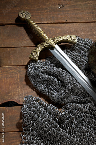 sword and the soldier's helmet with horns on a wooden background Poster