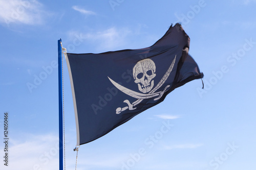 Pirate flag waving on blue sky Poster